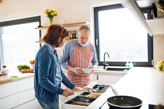 A portrait of senior couple in love indoors at home, cooking.