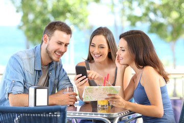 Group of tourists checking phone and map on vacation