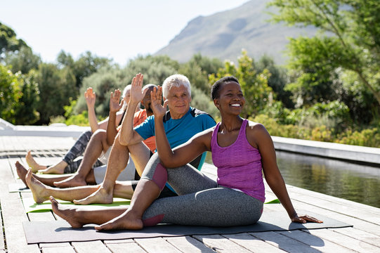Mature group of people doing yoga exercise