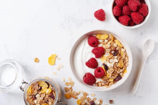 Greek yogurt in bowl with raspberries and muesli on white table top view. Healthy  breakfast.