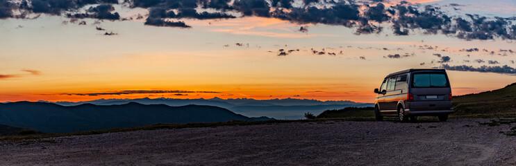 Wohnmobil auf einem Hügel bei Sonnenaufgang.
