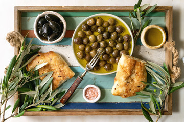 Variety of green and black whole olives in olive oil served in ceramic bowls with fresh baked ciabatta bread, pink salt and young olive wood branches over wooden plank tray. Flat lay, space