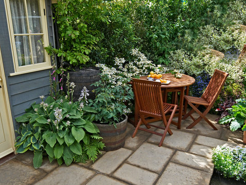 Seating and outdoor eating in a small patio garden with planted containers on the terrace