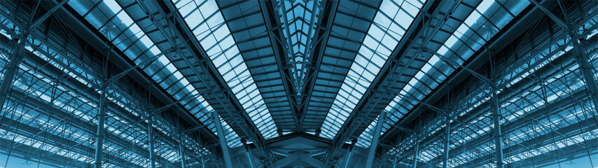 Wide screen of large cargo warehouse roof. Made from steels and glasses. Adjust color theme to blue tone.