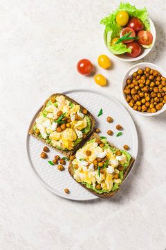 Breakfast toasts, soft scrambled eggs avocado goat cheese spicy chickpeas. Top view, space for text.