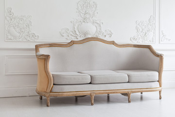 Luxurious bright Rococo interior with a large sofa and stucco on the walls. Selective focus.