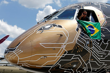 An Embraer E195-2 seen on display, sporting a livery combining a lion's head with an integrated circuit design, during the 53rd International Paris Air Show at Le Bourget Airport near Paris