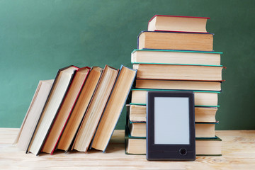 books pile and e-book on wooden desk, e-learning concept