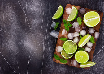 Wall Mural - Fresh lime, mint and ice on cutting board on dark background.