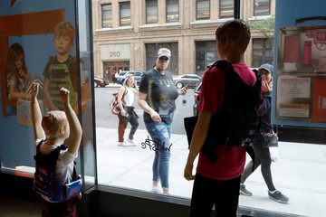 "People look at mannequins wearing bullet proof vests as part of an art installation by artist WhIsBe titled ""Back to School Shopping"" to illustrate the dangers of gun violence in schools, at a gallery in New York City"