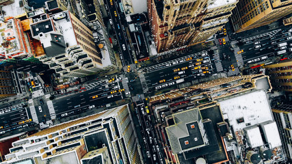 Aerial view of New York downtown building roofs. Bird's eye view from helicopter of cityscape metropolis infrastructure, traffic cars, yellow cabs moving on city streets and crossing district avenues Wall mural