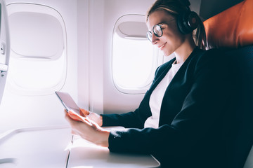 Cheerful female passenger in eyewear and headphones for noise cancellation watching movie on digital tablet while connecting to wifi internet on board, happy woman sitting near airplane window