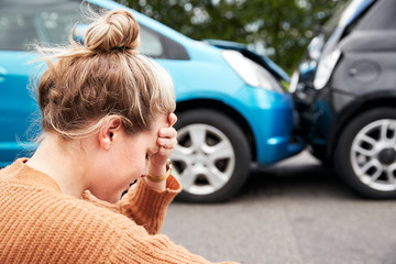 Female Motorist With Head In Hands Sitting Next To Vehicles Involved In Car Accident Fototapete