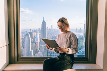 Smiling female office coworker working on modern tablet computer while sitting on window sill with panoramic views on New York city. Hipster girl browsing social network on touch pad, online banking