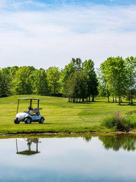 golf cart reflecting in large water hazard