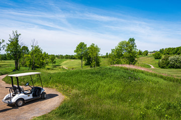 golf cart overlloking rolling hills of golf course