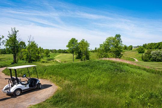 golf cart overlloking rolling hills of golf course