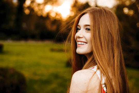Portrait of a lovely female with long red hair and freckles looking away laughing against sunset outside.