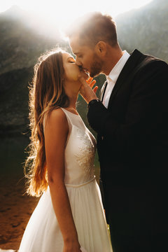 Side view portrait of a amazing wedding couple kissing against sunset while groom is touching bride's face with a hand.