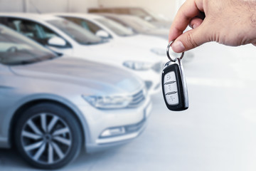 Man's hand holding car key.Automobile rent or leasing concept. Fototapete