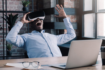 223be101b683 African buisiness man spending free time in office enjoying virtual reality  headset shouting happily