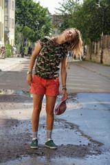 Jugendliche steht im Sommerregen in der Straße und genießt Abkühlung