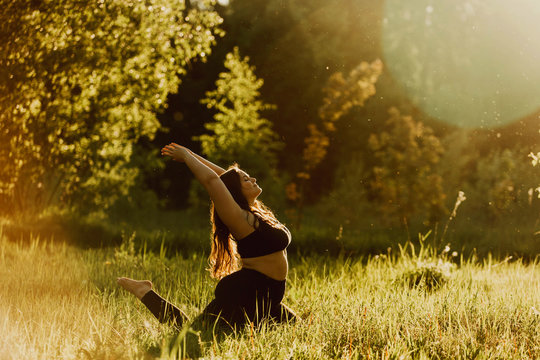 Beautiful plus size girl doing yoga in nature on a sunny summer day. Body positive, sports for women, harmony, asana, healthy lifestyle, inspiring look, self-love and wellness.