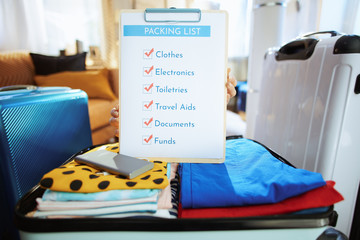 Closeup on young traveller woman showing packing list