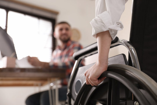 Woman in wheelchair with her colleague at workplace, closeup