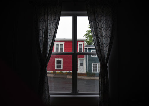 Looking out at rainy weather through window with drapes