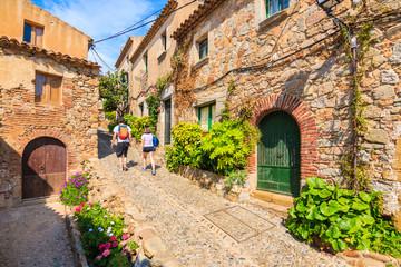 Wall Mural - Couple of tourist backpackers walking in narrow street of old town in Tossa de Mar, Costa Brava, Spain.