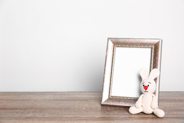 Photo frame and adorable toy bunny on table against light background, space for text. Child room elements