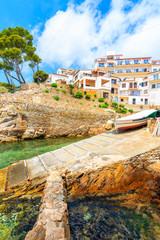 Fototapete - View of beach with fishing boat and holiday apartments in Fornells village, Costa Brava, Spain