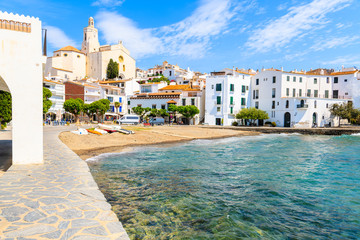 White houses and blue sea in Cadaques port with church and beach, Costa Brava, Spain
