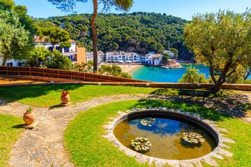 Wall Mural - Water pond in garden and view of sea bay in Tamariu fishing village, Costa Brava, Spain