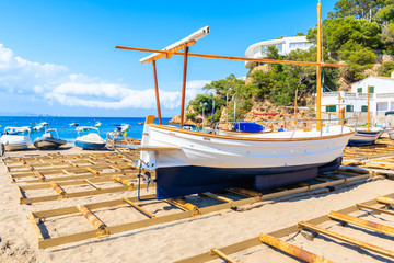 Wall Mural - Traditional fishing boat on Sa Riera beach with sea and village houses in background, Costa Brava, Spain