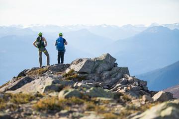 Two climbers stand on the summit of Douglas Peak, British Columbia.
