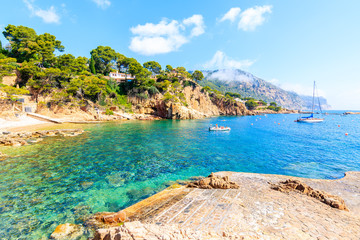 Fototapete - Beach and boats on sea in picturesque bay near Fornells village, Costa Brava, Spain