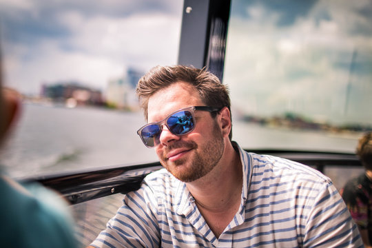 35 year old man on water taxi in Baltimore smiling with sunglasses