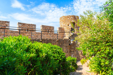 Wall Mural - Castle walls and green alley in old town of Tossa de Mar, Costa Brava, Spain