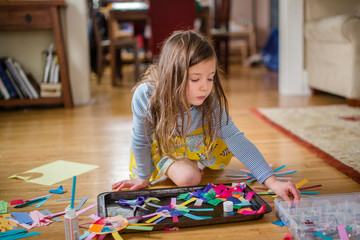 A little girl peacefully sits on living room floor with an art project