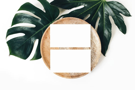 Blank white business cards mockups, wooden plate, aralia and monstera leaf isolated on white table backgound. Modern template for branding identity. Tropical design. Wedding stationery. Flat lay, top