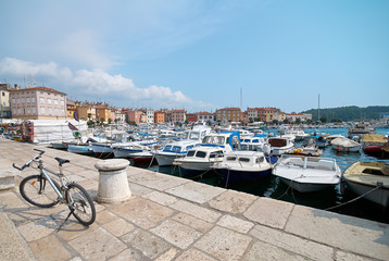The bike is parked on the pier in port of Rovinj, Croatia. Yachts landing, motorboats and boats on water, medieval vintage houses of old town on the background.