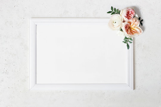 Wedding, birthday sign board mock-up scene. Blank white wooden frame. Decorative floral corner. Green leaves, pink English roses and ranunculus flowers. Concrete table background. Flat lay, top view