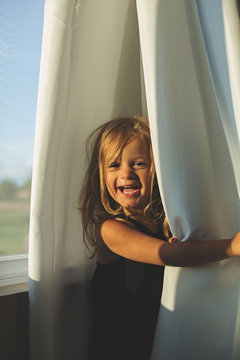 Happy toddler amuses herself by playing, unplugged, in curtains.