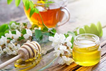 Acacia tree flowers honey jar, wooden dipper and healthy herbal tea cup.