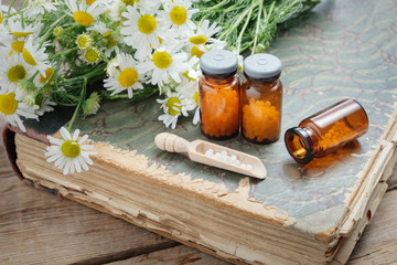 Chamomile flowers, bottles of homeopathic globules and old books.