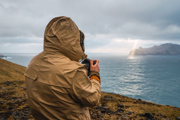 Back view of anonymous man in winter clothes using a photo camera outdoors in Faroe Islands landscape
