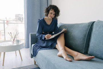 Elegant woman sitting on a sofa drawing on a notebook at home