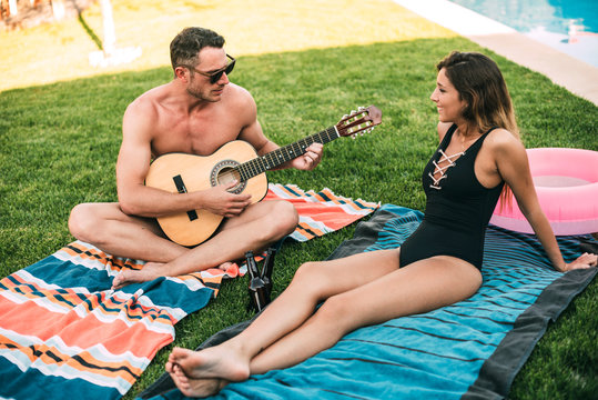 Guy with guitar playing for his girlfriend
